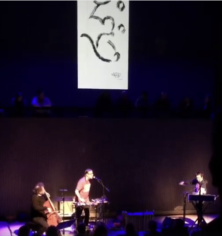 Mike Patton on the mic while Laurie Anderson plays violin at SF Jazz under the drawing of Lou Reed and his exploding heart